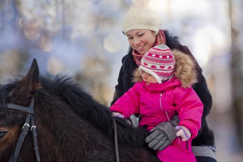 Kleines Kind mit Reitoverall sitzt auf Pferd.